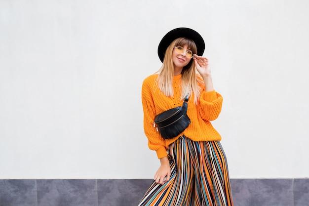 Stijlvolle vrouw op wit in stijlvolle oranje trui en veelkleurige streep culotte