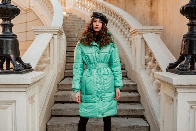 Stijlvolle vrouw poseren in winter herfst mode trend blauwe puffer jas en hoed baret in oude mooie straat trappen Gratis Foto