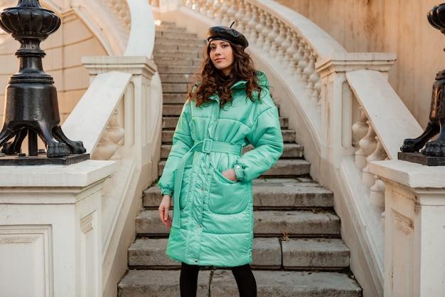 Stijlvolle vrouw poseren in winter herfst mode trend blauwe puffer jas en hoed baret in oude mooie straat trappen