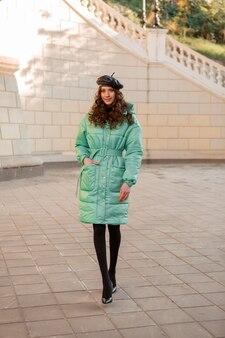 Stijlvolle vrouw poseren in winter herfst mode trend blauwe puffer jas en hoed baret in oude mooie straat volle hoogte