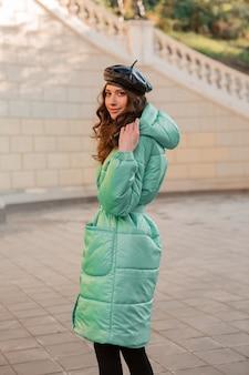 Stijlvolle vrouw poseren in winter herfst mode trend blauwe puffer jas en hoed baret in oude mooie straat
