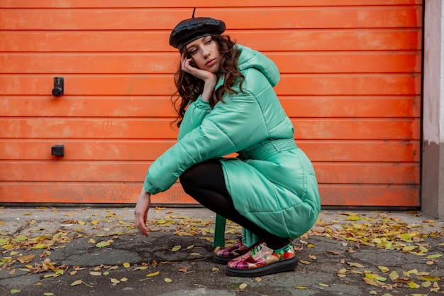 Stijlvolle vrouw poseren in winter herfst mode trend puffer jas en hoed baret tegen oranje muur in straat kleurrijke gedrukte schoenen dragen