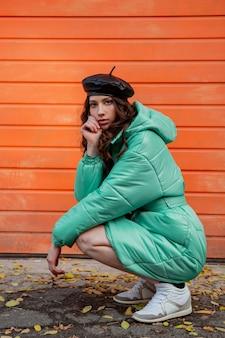 Stijlvolle vrouw poseren in winter herfst mode trend puffer jas en hoed baret tegen oranje muur in straat sneakers dragen