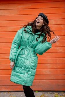 Stijlvolle vrouw poseren in winter herfst mode trend puffer jas en hoed baret tegen oranje muur in straat