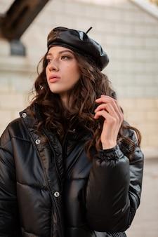 Stijlvolle vrouw poseren in winter herfst mode trend zwarte puffer jas en lederen hoed baret in oude mooie straat hoge hakken dragen