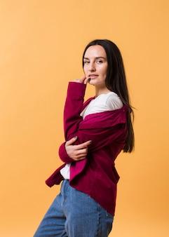 Stijlvolle vrouw poseren met een oranje achtergrond