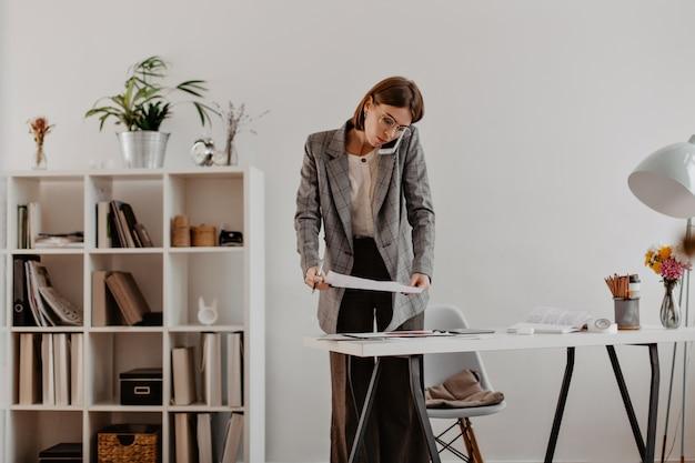 Stijlvolle vrouw praten over telefoon met partners op de werkplek, contract overwegen.