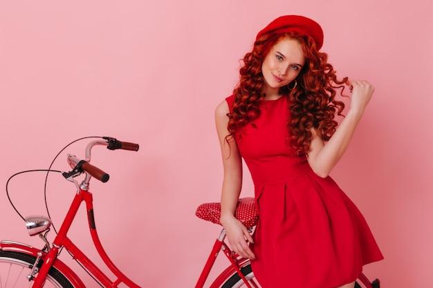 Stijlvolle vrouw raakt flirterig haar krul aan en kijkt naar de camera, leunend op rode fiets op roze ruimte.
