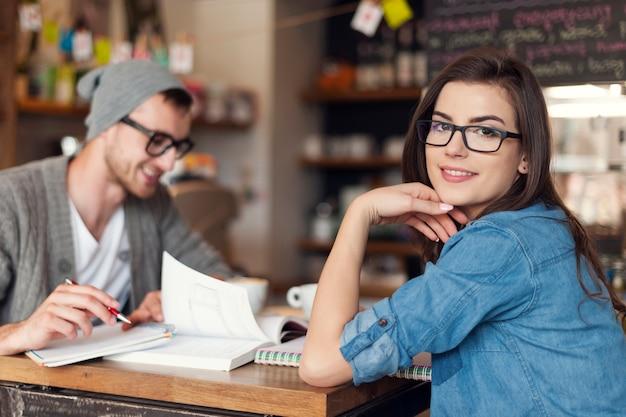 Stijlvolle vrouw studeert met haar vriend in café