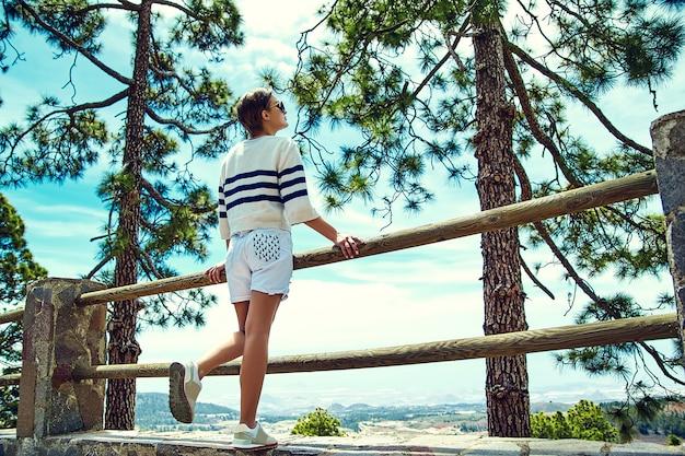 Stijlvolle vrouw vrouw in casual hipster kleding staan in de buurt van hek