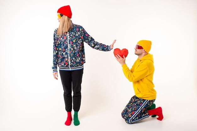 Stijlvolle vrouw weigert een schenkend hart van vriendje in kleurrijke kleding over witte muur