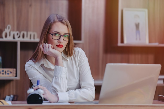 Stijlvolle vrouw werkt op een laptop bureau in een modern kantoor