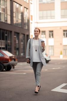 Stijlvolle vrouw. zelfverzekerde stijlvolle knappe blanke jonge vrouw met een papieren kopje koffie die langs de straat loopt