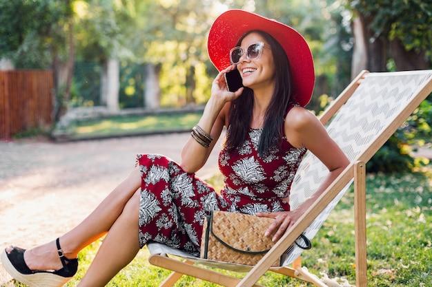 Stijlvolle vrouw zittend in ligstoel praten over slimme telefoon in tropische stijl outfit, zomer modetrend, top, rok, mager, stro handtas, rode hoed, zonnebril, accessoires, glimlachen, vakantie