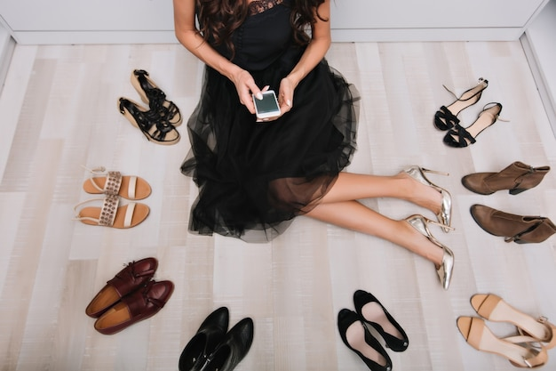 Stijlvolle vrouw zittend op de vloer in kledingkast met smartphone in handen, bericht schrijven, omringd door veel schoenen. ze droeg een zwarte pluizige rok en zilveren luxe schoenen.