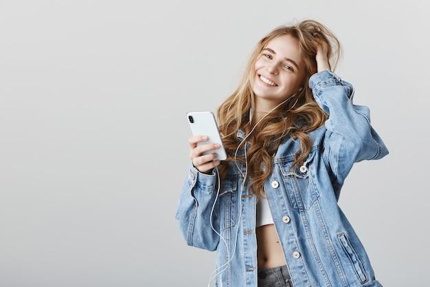 Stijlvolle vrouwelijke blogger met behulp van mobiele telefoon en muziek luisteren in oortelefoons