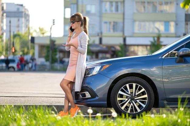 Stijlvolle vrouwelijke chauffeur die in de zomer in de buurt van haar voertuig staat en op mobiele telefoon praat