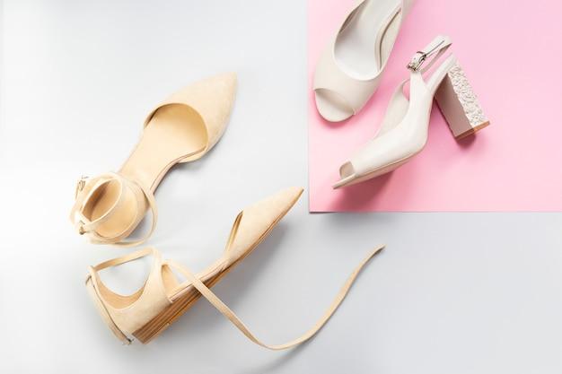Stijlvolle vrouwelijke platte beige sandalen en witte hakken bruiloft schoenen geïsoleerd op blauwe en roze achtergrond.