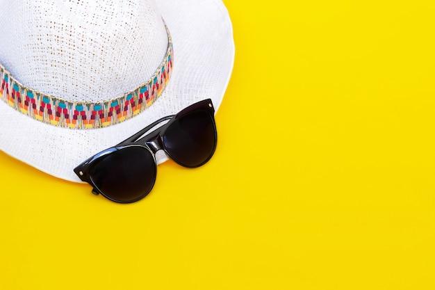 Stijlvolle vrouwelijke strowitte hoed met een veelkleurig patroon en trendy zwarte zonnebril geïsoleerd op een felle gele muur