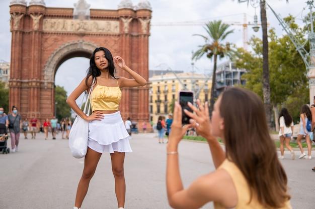 Stijlvolle vrouwelijke toeristen fotograferen in de stad