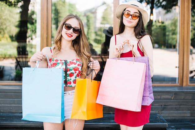 Stijlvolle vrouwen tonen boodschappentassen