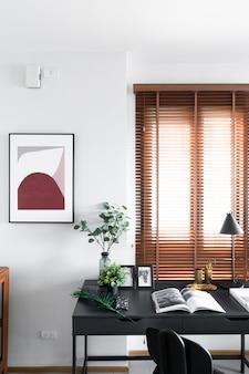 Stijlvolle werkhoek versieren met zwart houten frame en kunstplant in glazen vaas