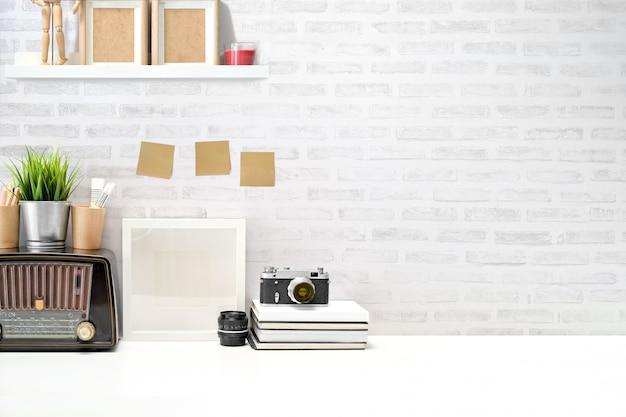 Stijlvolle werkplek vintage camera, leeg scherm tablet en gadget