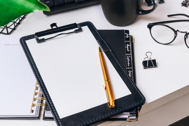 Stijlvolle werkruimte met desktopcomputer, toetsenbord, kopje koffie, kantoorbenodigdheden