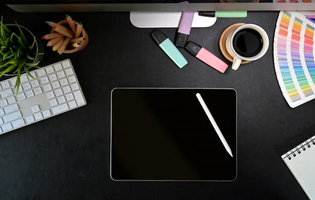 Stijlvolle werkruimte met digitale grafische tekentablet, creavtive benodigdheden op donkere lederen werkplek