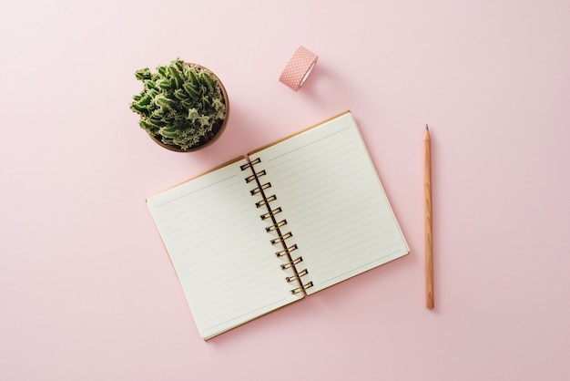 Stijlvolle werkruimte met koffiekopje, telefoon en lege witte briefpapier op pastel zacht roze achtergrond, kopieer ruimte. sjabloon voor uw ontwerp.