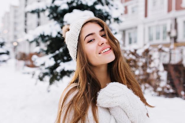 Stijlvolle winter portret van charmante jonge vrouw met lang donkerbruin haar, in wollen witte handschoenen en hoed lopen op straat vol met sneeuw. vrolijke stemming, glimlachend.