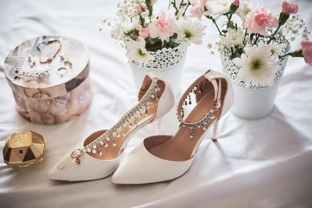 Stijlvolle witte bruids schoenen, parfums, bloemen en juwelen.