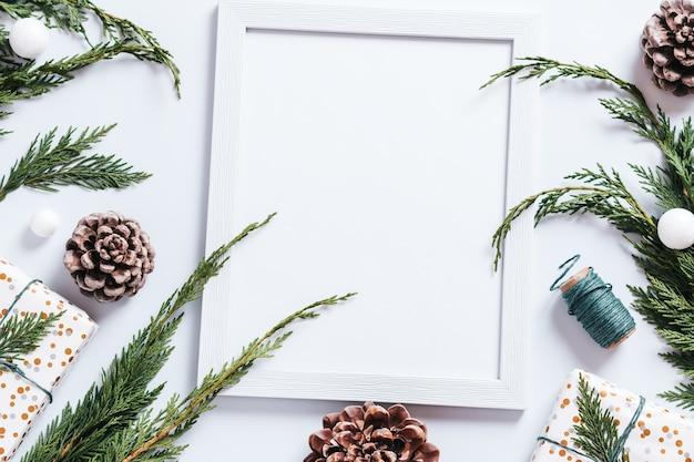 Stijlvolle witte en groene kerstplattegrond met enorme dennenappels, cedertakken, cadeautjes en decoraties