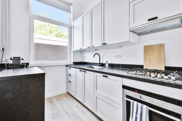 Stijlvolle witte kasten met chromen inbouwapparatuur gelegen nabij raam in lichte moderne keuken in appartement