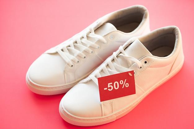 Stijlvolle witte mode sneakers op roze.