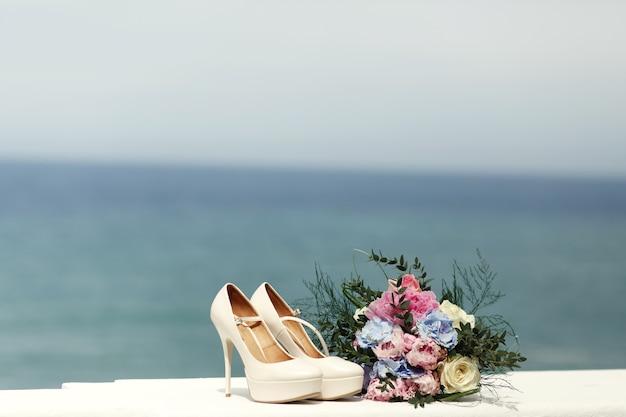 Stijlvolle witte schoenen op hoge hakken staan op de witte leuningen wi