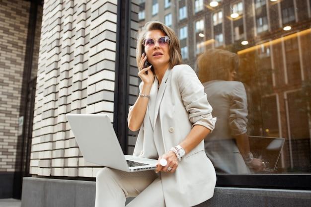 Stijlvolle zakelijke dame buiten werken met haar laptop en haar smartphone