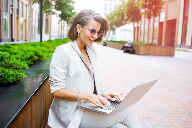 Stijlvolle zakelijke dame buiten werken met haar laptop