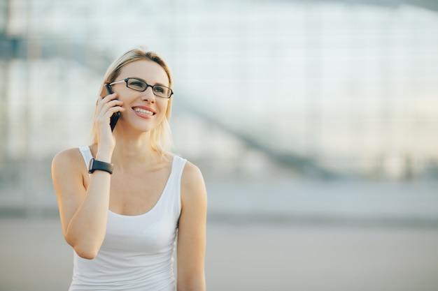 Stijlvolle zakelijke dame in glazen praten aan de telefoon en glimlachen