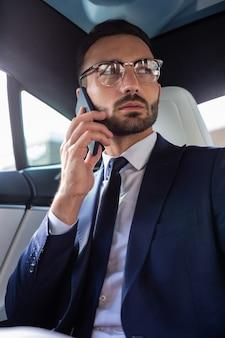 Stijlvolle zakenman. bebaarde stijlvolle donkerharige zakenman met pak en stropdas die zijn vrouw belt