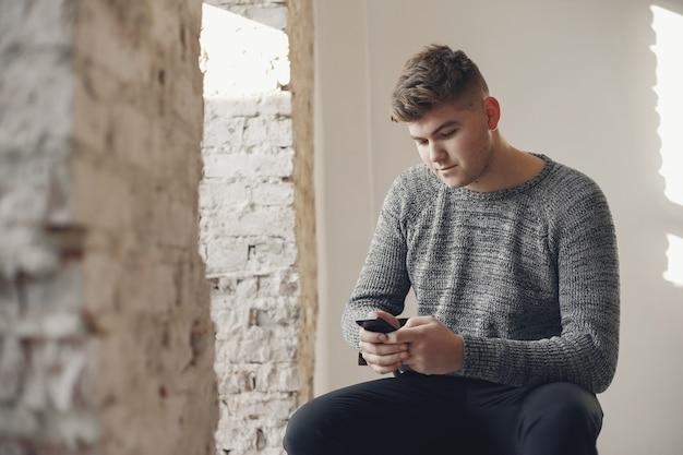 Stijlvolle zakenman die in een kantoor werkt en de telefoon gebruikt