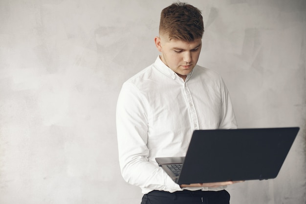 Stijlvolle zakenman die in een kantoor werkt en laptop gebruikt