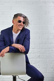 Stijlvolle zakenman met krullend lang haar in zonnebril zittend op een stoel