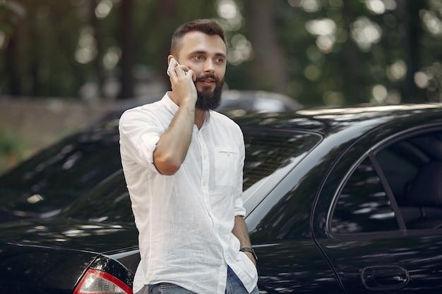Stijlvolle zakenman permanent in de buurt van de auto en gebruik mobiele telefoon