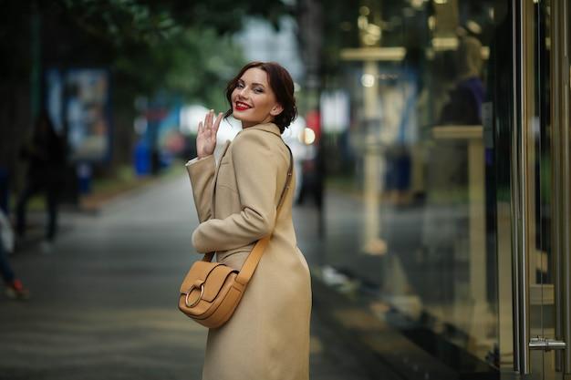 Stijlvolle zakenvrouw 25 jaar oud in een witte jas op een achtergrond van een straat met winkels