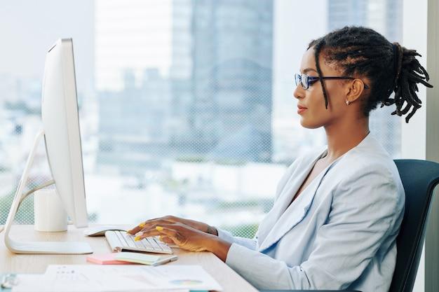 Stijlvolle zakenvrouw die op laptop werkt