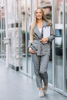 Stijlvolle zakenvrouw met klembord in de stad