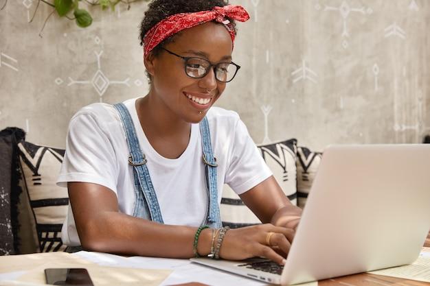 Stijlvolle zakenvrouw werkt op laptopcomputer in gezellige coffeeshop, informatie over toetsenborden