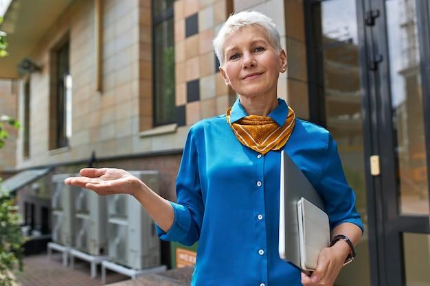 Stijlvolle zelfverzekerde zakenvrouw van middelbare leeftijd met kort kapsel poseren buiten kantoorgebouw met laptop onder haar arm, gebaar maken alsof ze iets bij de hand houden