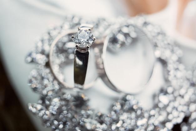 Stijlvolle zilveren trouwringen van witgoud liggen op de kristallen armband